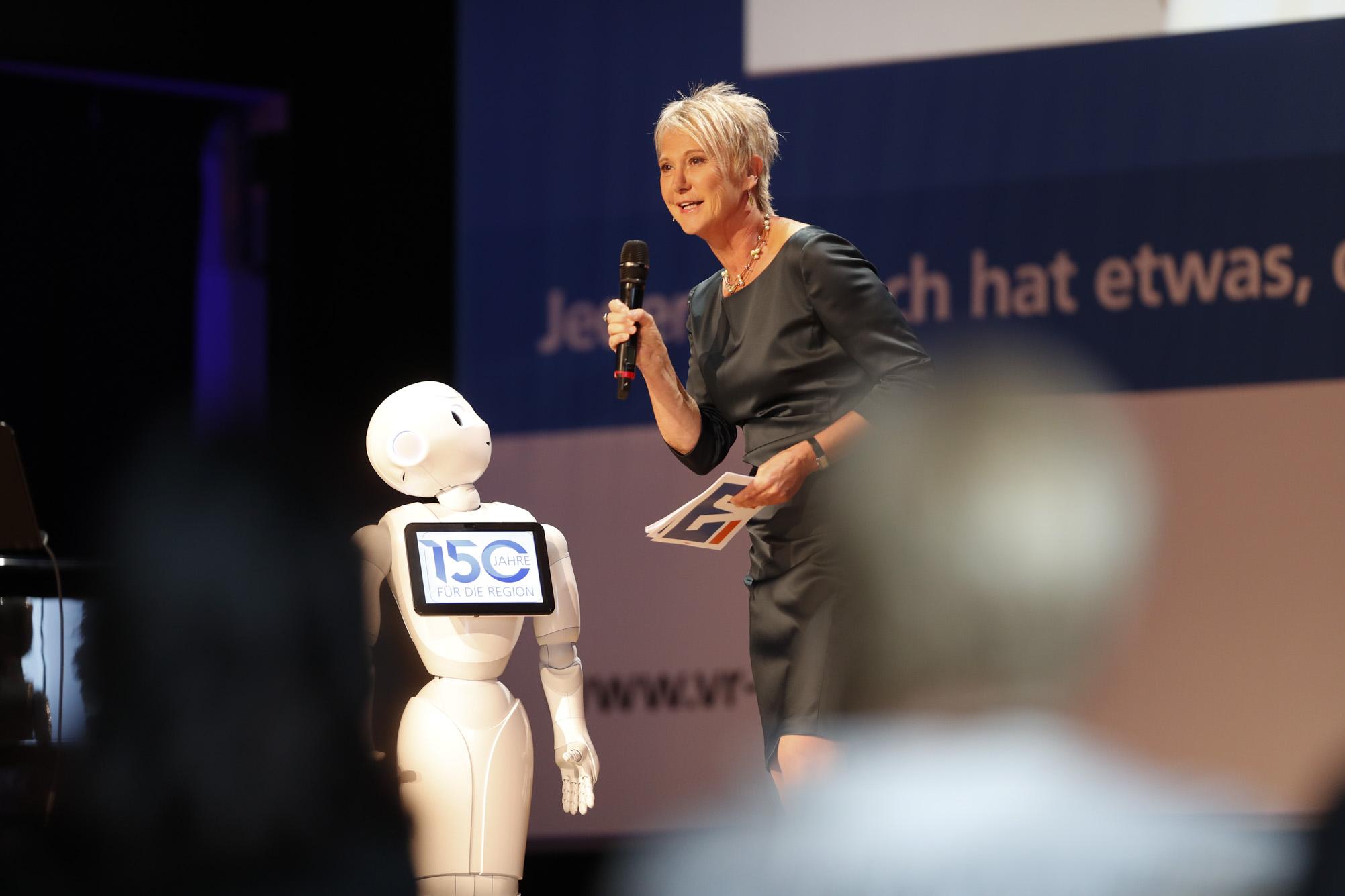 "Moderation der Jubiläums-Gala ""150 Jahre Volksbank-Raiffeisenbank Laupheim-Illertal"" im Gespräch mit dem Roboter ""Vrida"", Kulturhaus Laupheim, Juni 2018"